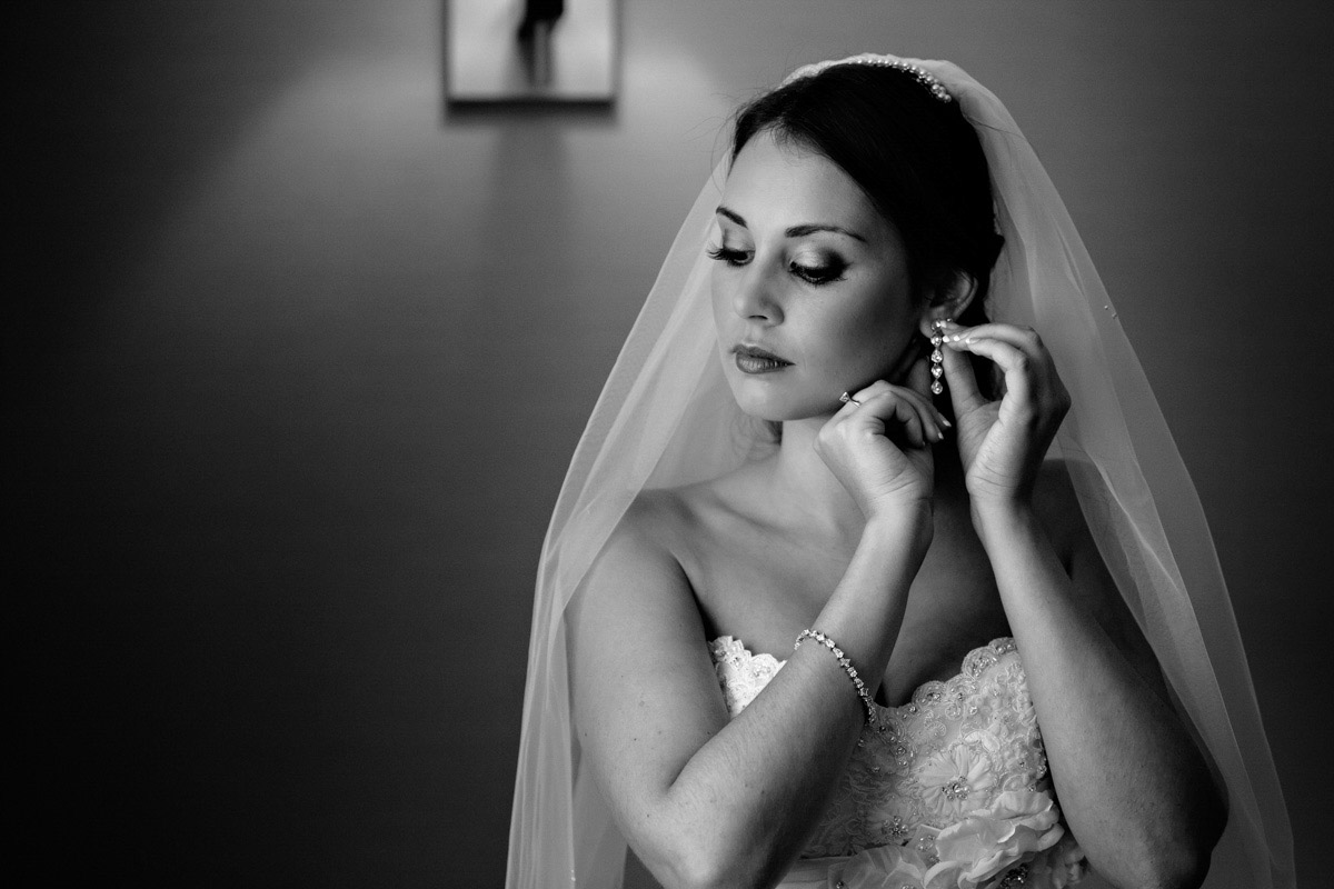 Bride putting on her jewellery on the morning of the wedding