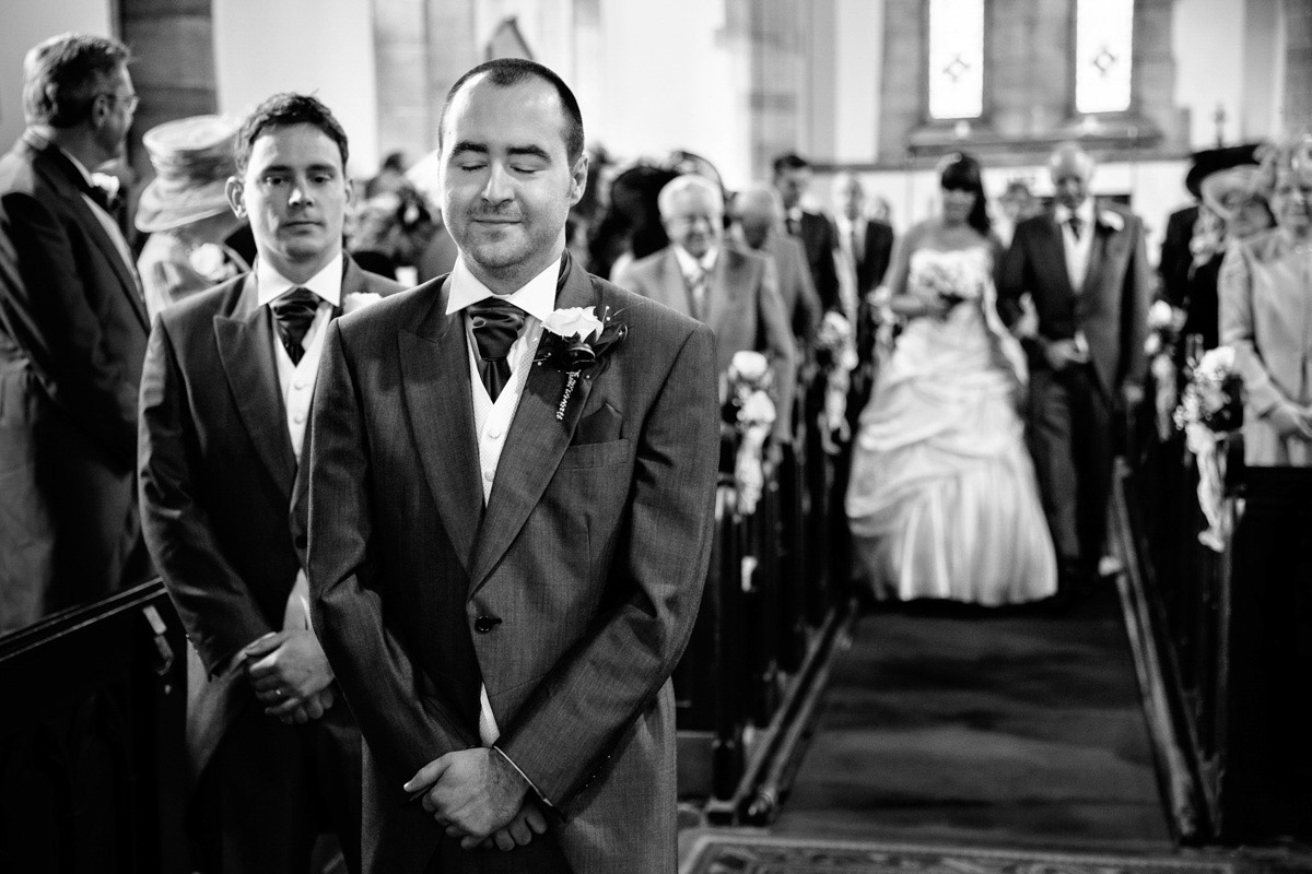 Groom waiting nervously at church alter for his bride
