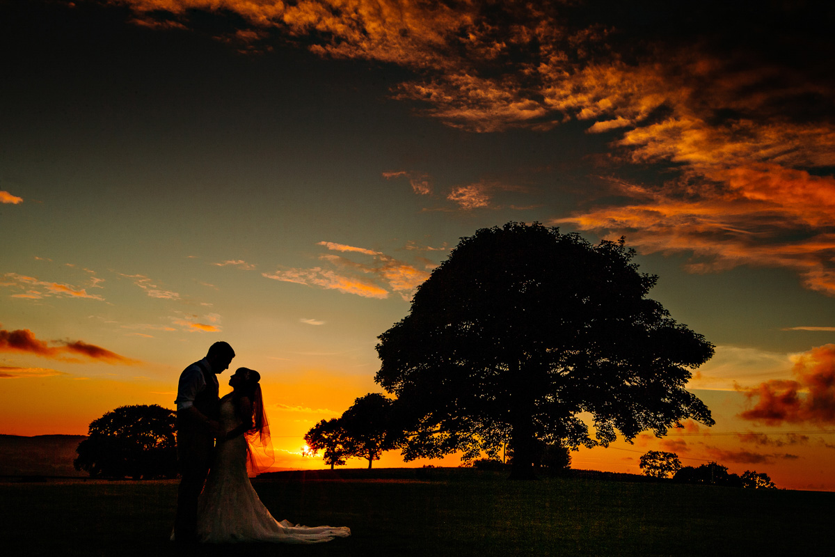 Beautiful sunset silhouette with the bride and groom at Heaton House Farm