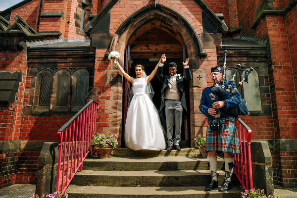 Bride and groom leaving the church with bagpipes as the wave