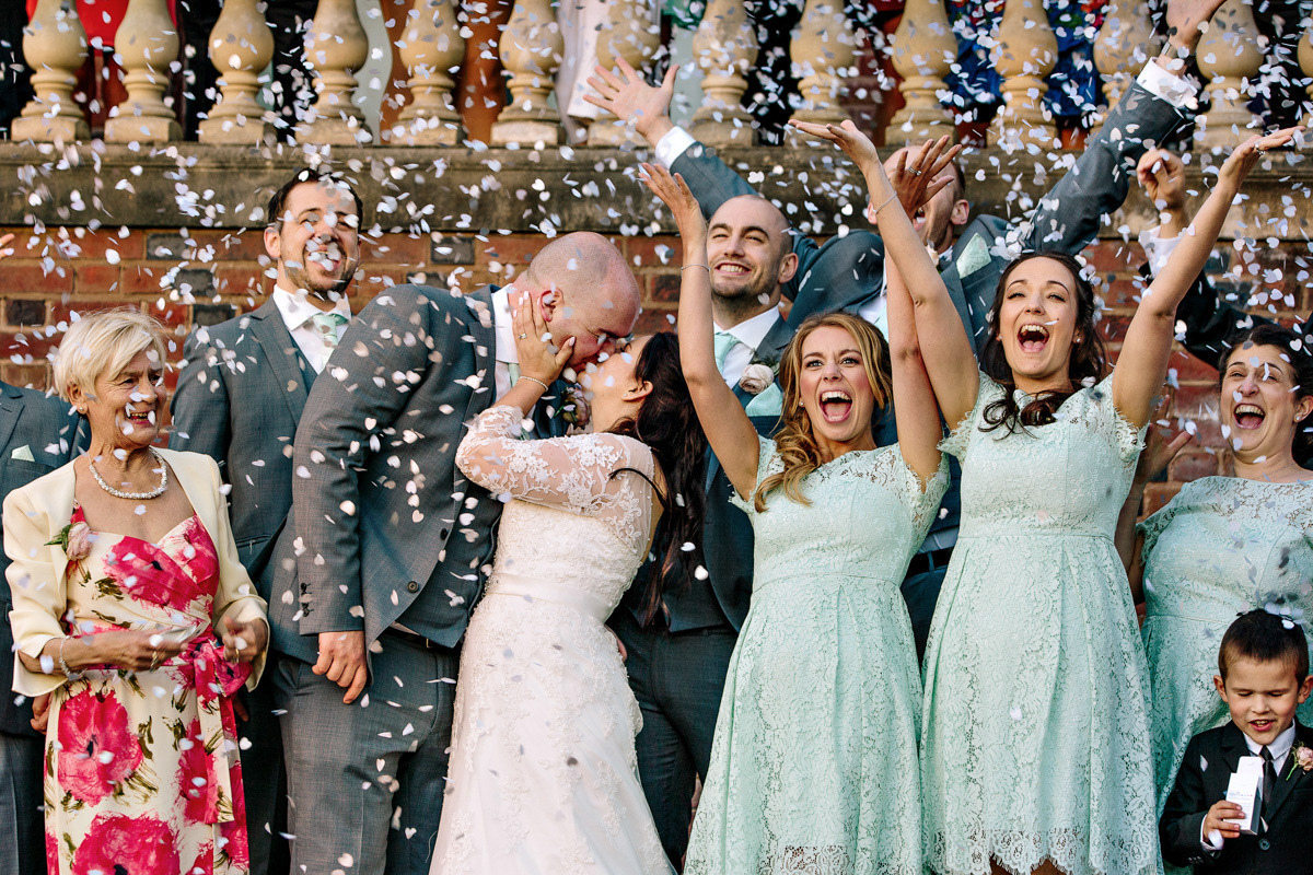 Bridesmaids waving as the Bride and groom are covered in confetti