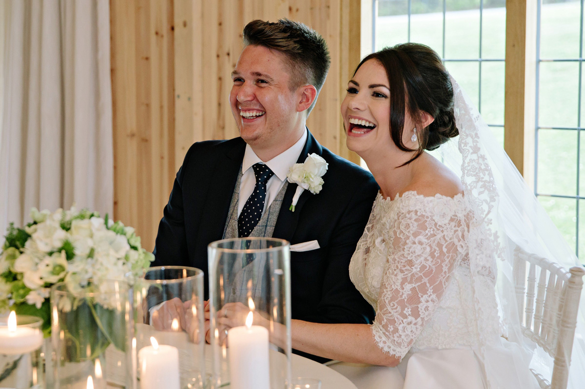 Bride and Groom as they sign the wedding register sharing laughs with guests