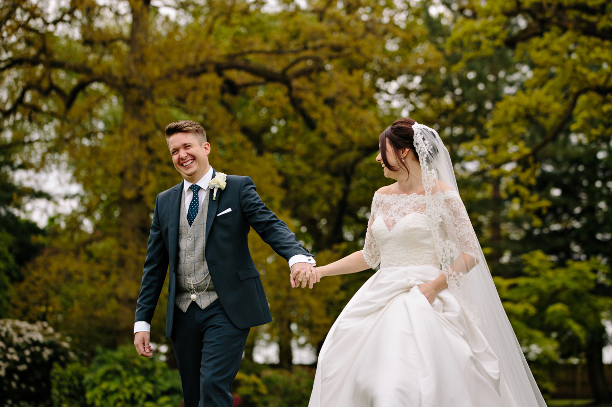 Bride and Groom walking and laughing in the stunning grounds of their wedding venue