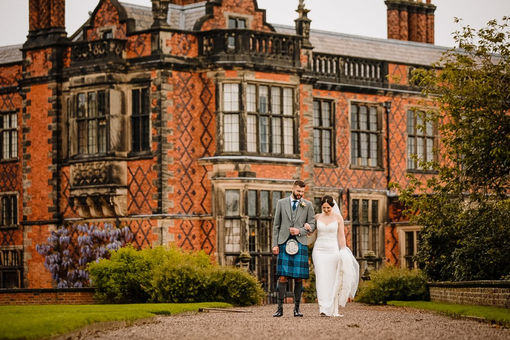Bride and Groom photographed walking in the gardens in front of Arley Hall
