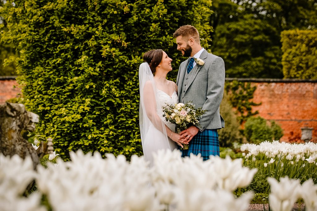 Bride and Groom in the gardens amongst the flowers at Arely Hall