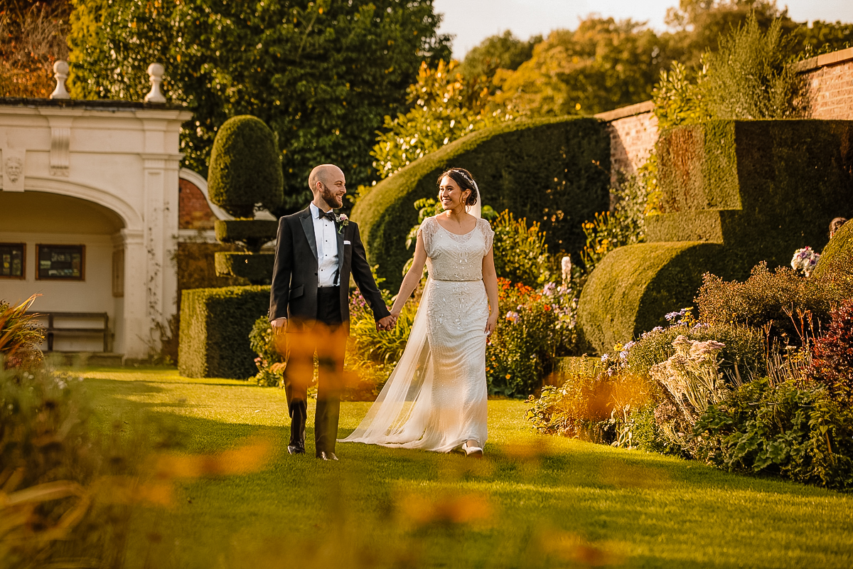 Arley Hall and Gardens with Bride and Groom walking holding hands