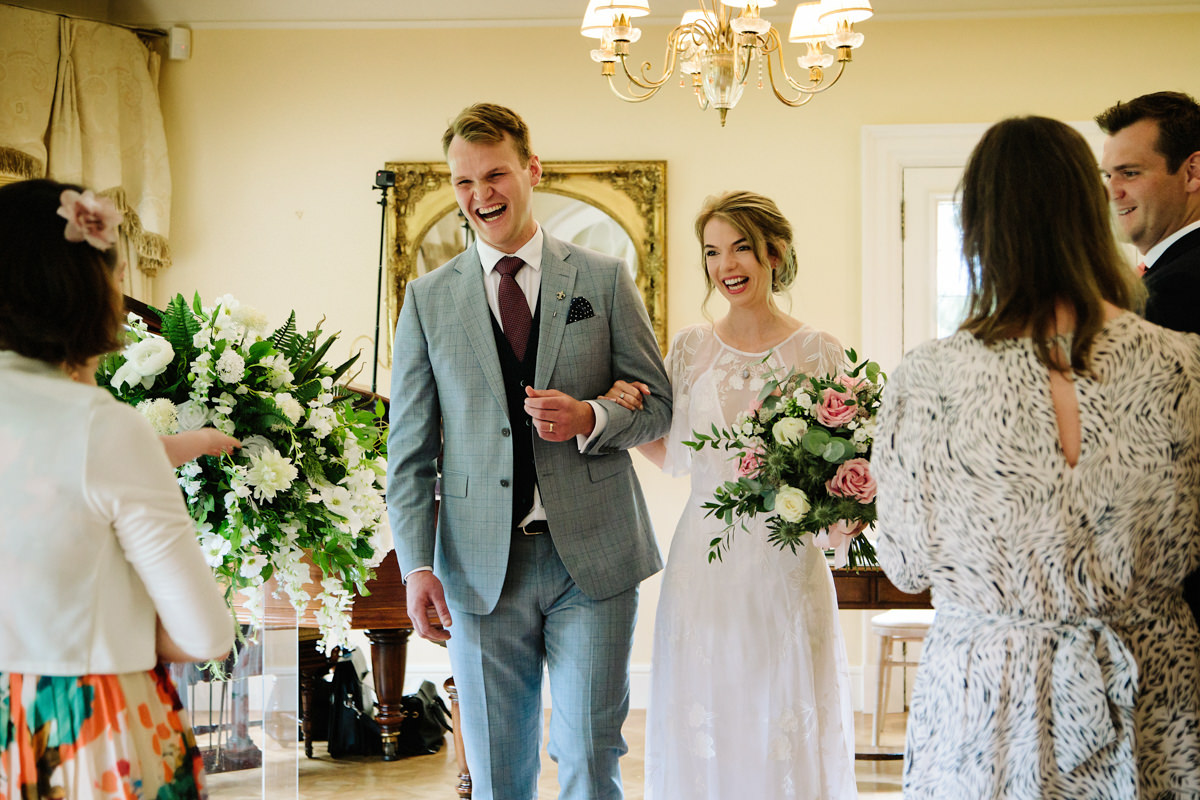Bride and Groom walking sown the aisle in the piano room at Colshaw Hall