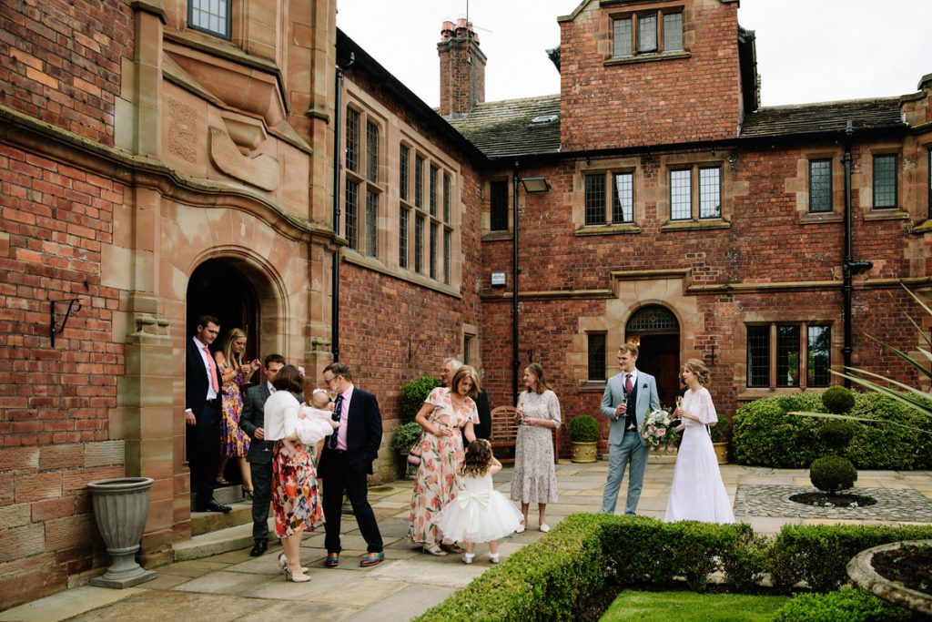 Guests in the courtyard at Colshaw Hall with their drinks reception