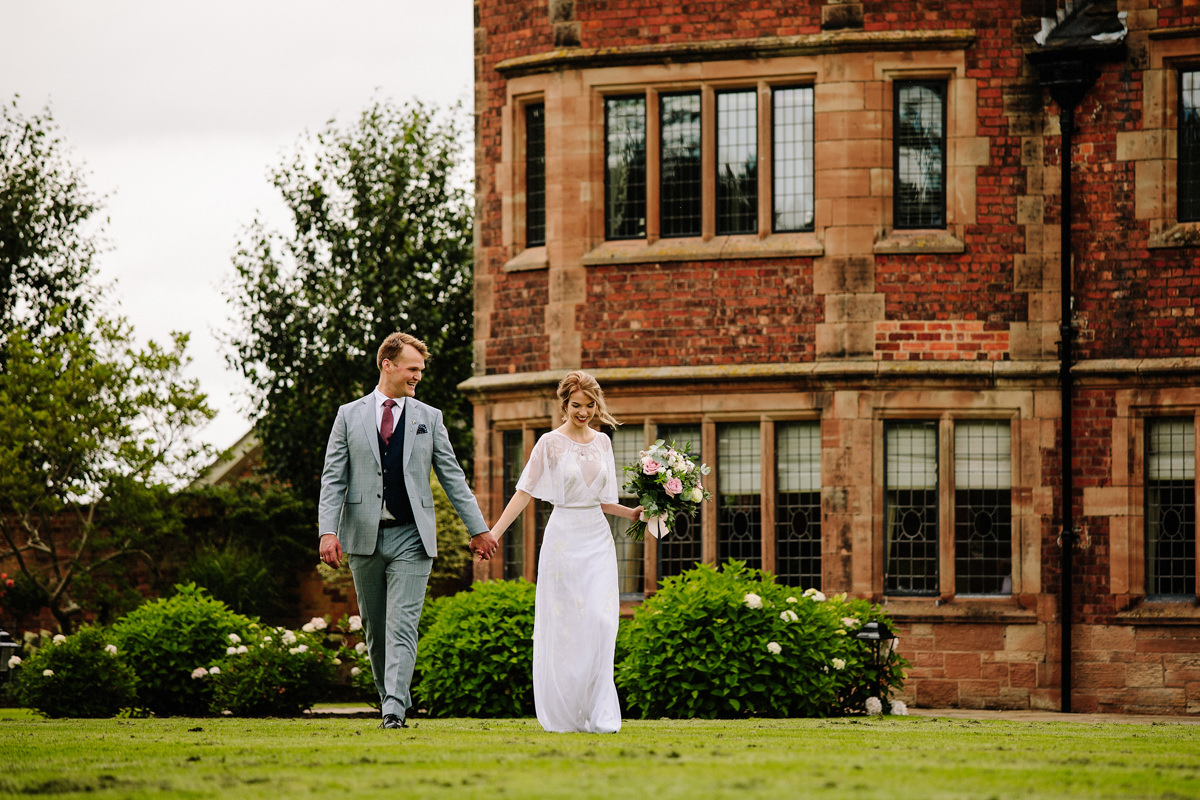 Bride and groom walking in the grounds of Colshaw Hall