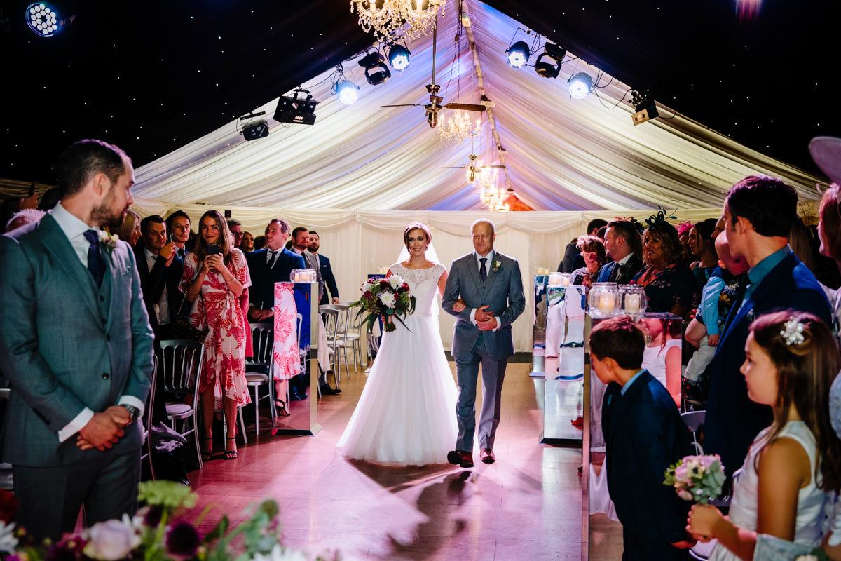 Bride walking down the aisle under the stars at Heaton House Farm