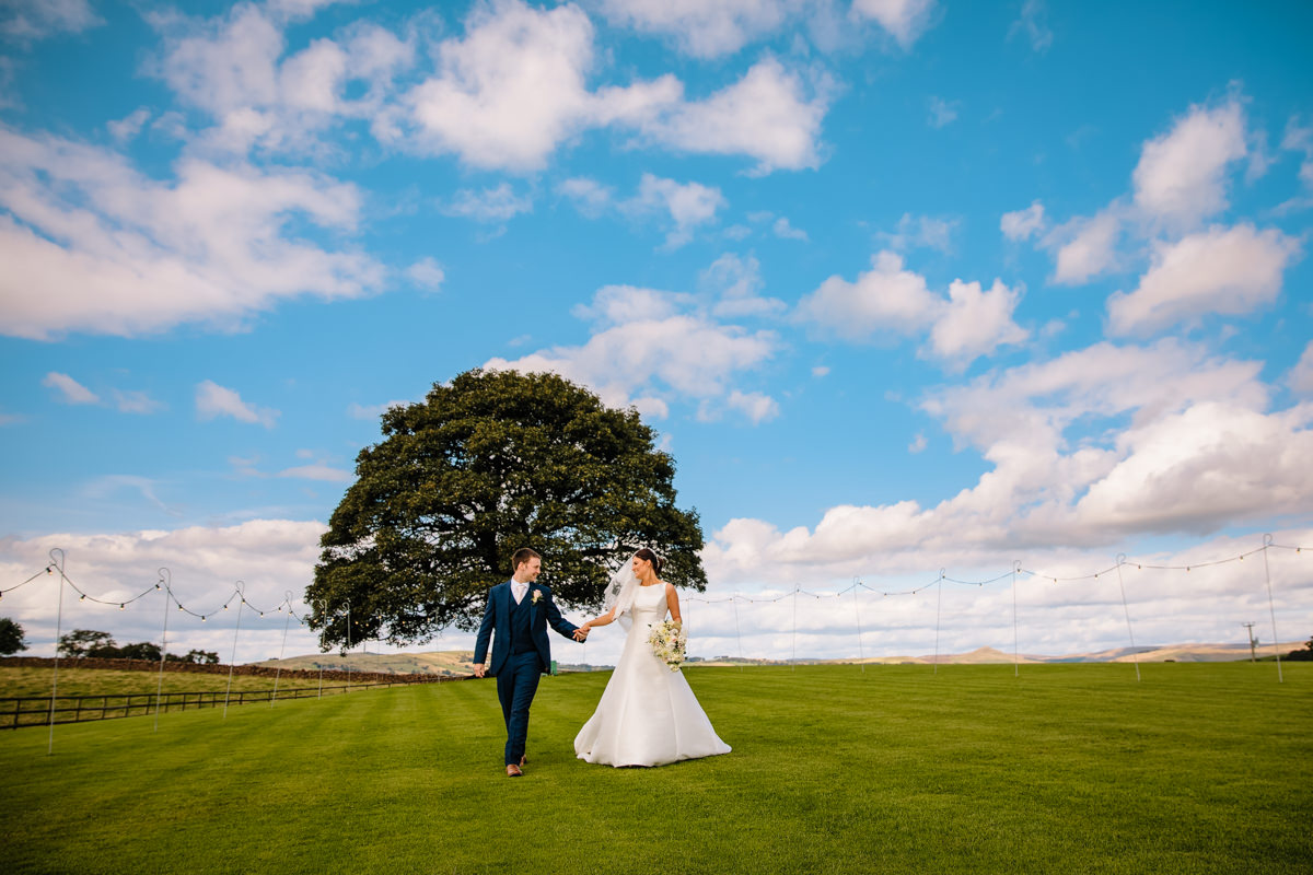 Heaton House Farm Sycamore tree with the Bride and Groom walking hand in hand