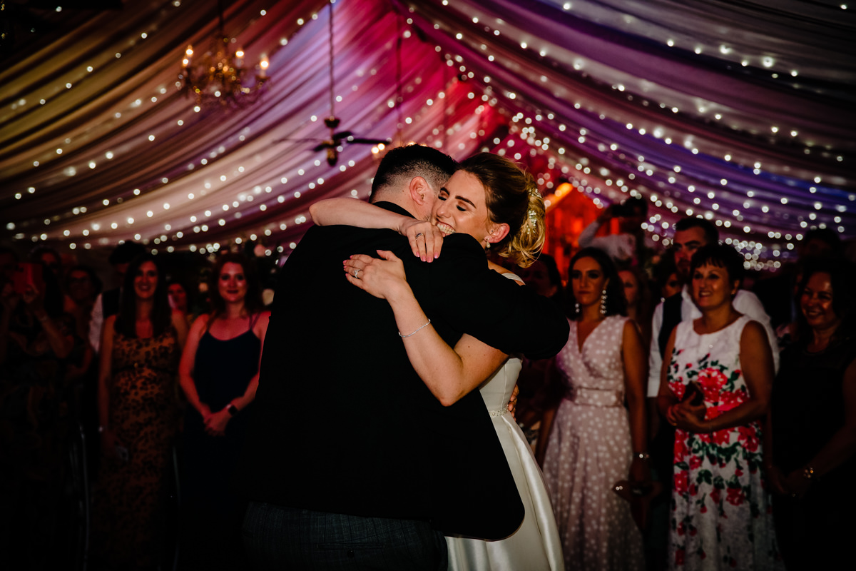 Bride hugging groom on the wedding dance floor during their first dance