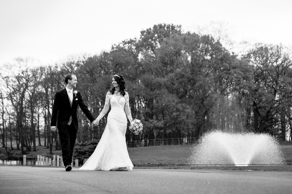 Bride and Groom walking by the fountain at Merrydale Manor