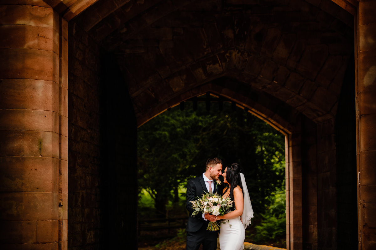 Bride and Groom in love holding each other near the drawbridge at Peckforton Castle
