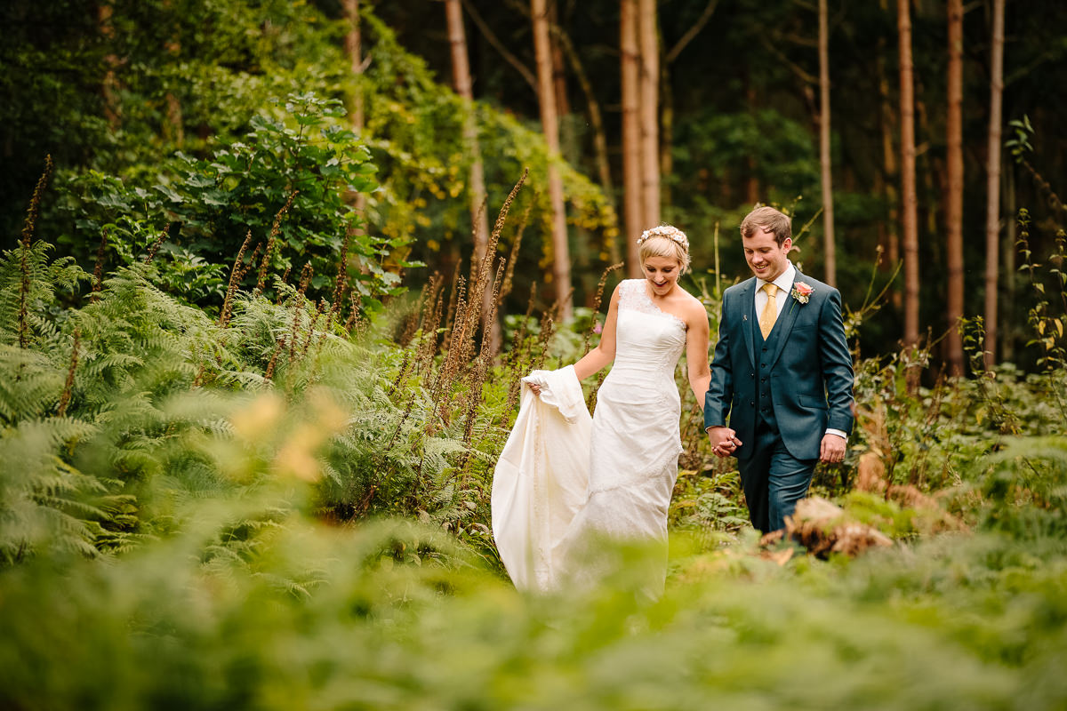 Bride and Groom walking together in the grounds of Peckforton Castle woods