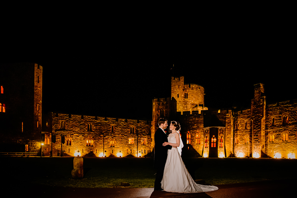 Peckforton Castle lit up in the evening with the bride and groom