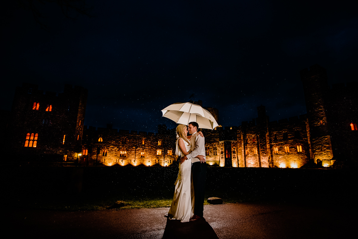 Backlit rain with the bride and groom holding an umbrella in form of Peckforton Castle