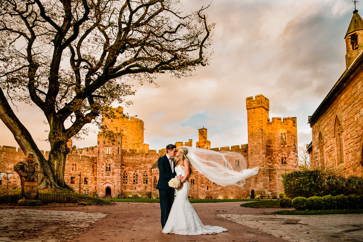 Peckforton Castle bride and groom loving moment together with the brides dress blowing in the wind