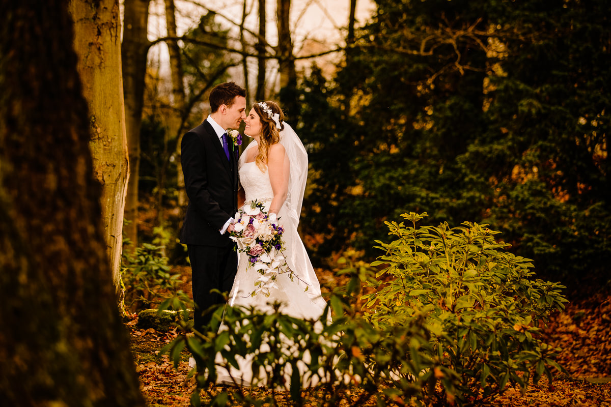 Bride and groom together in love in the woods at Peckforton Castle