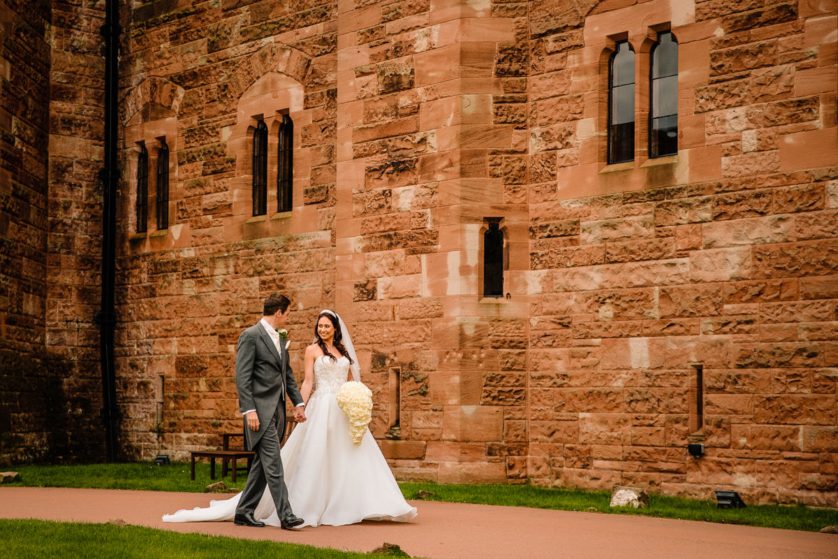 Bride and Groom walking hand in hand in the grounds of Peckforton Castle after just getting married