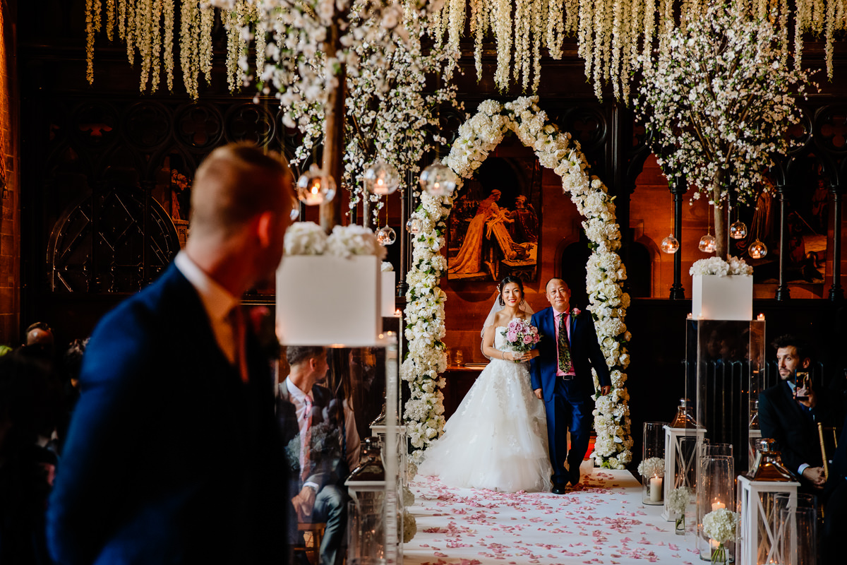 Bride walking down the wedding aisle with her father looked on by her husband to be in the great Hall at Peckforton Castle