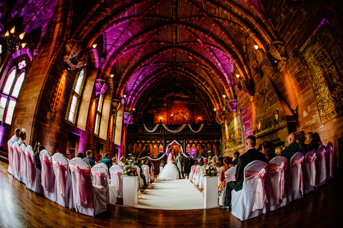 The Great Hall at Peckforton Castle during a ceremony with purple uplighters