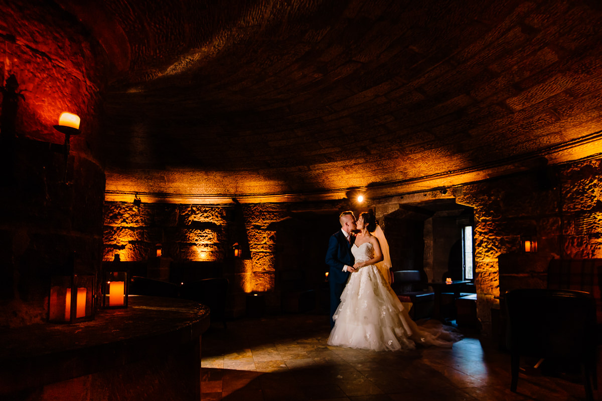 The wine cellar at Peckforton castle lit by candles with a bride and groom