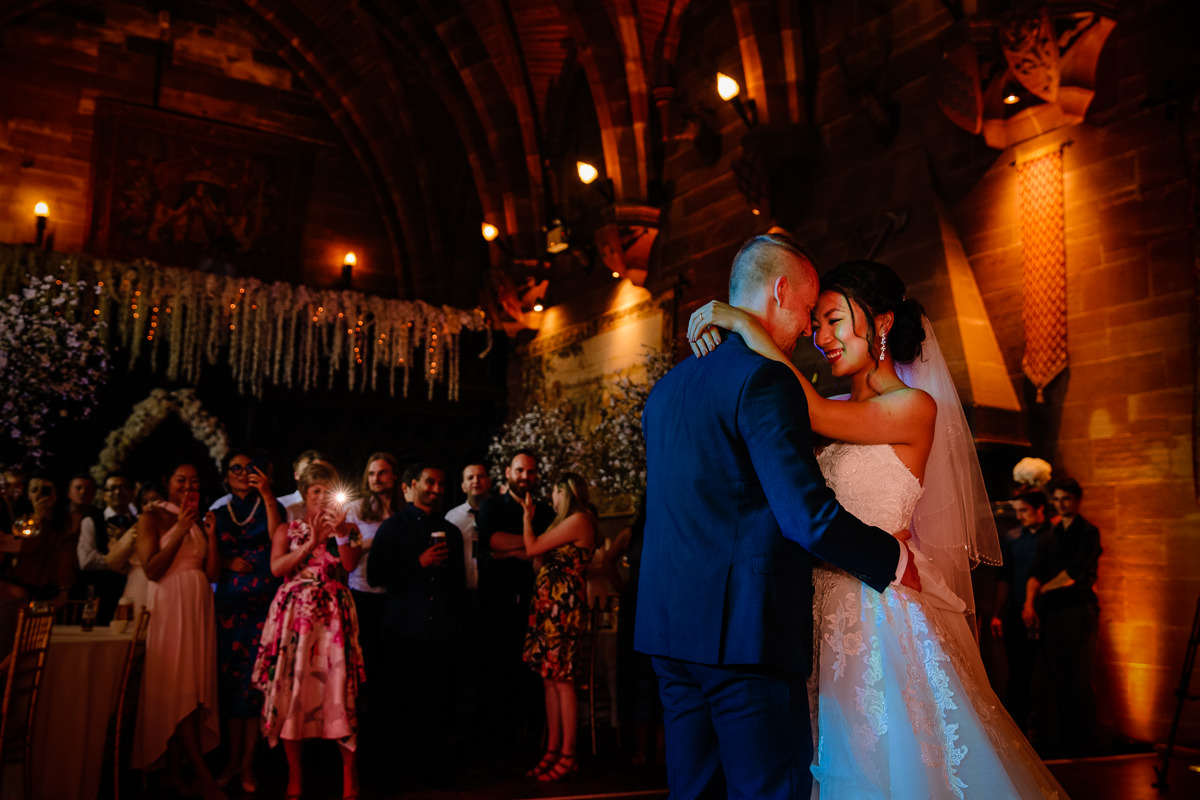 Intimate moment between the bride and groom during their first dance at Peckforton Castle in the Great Hall