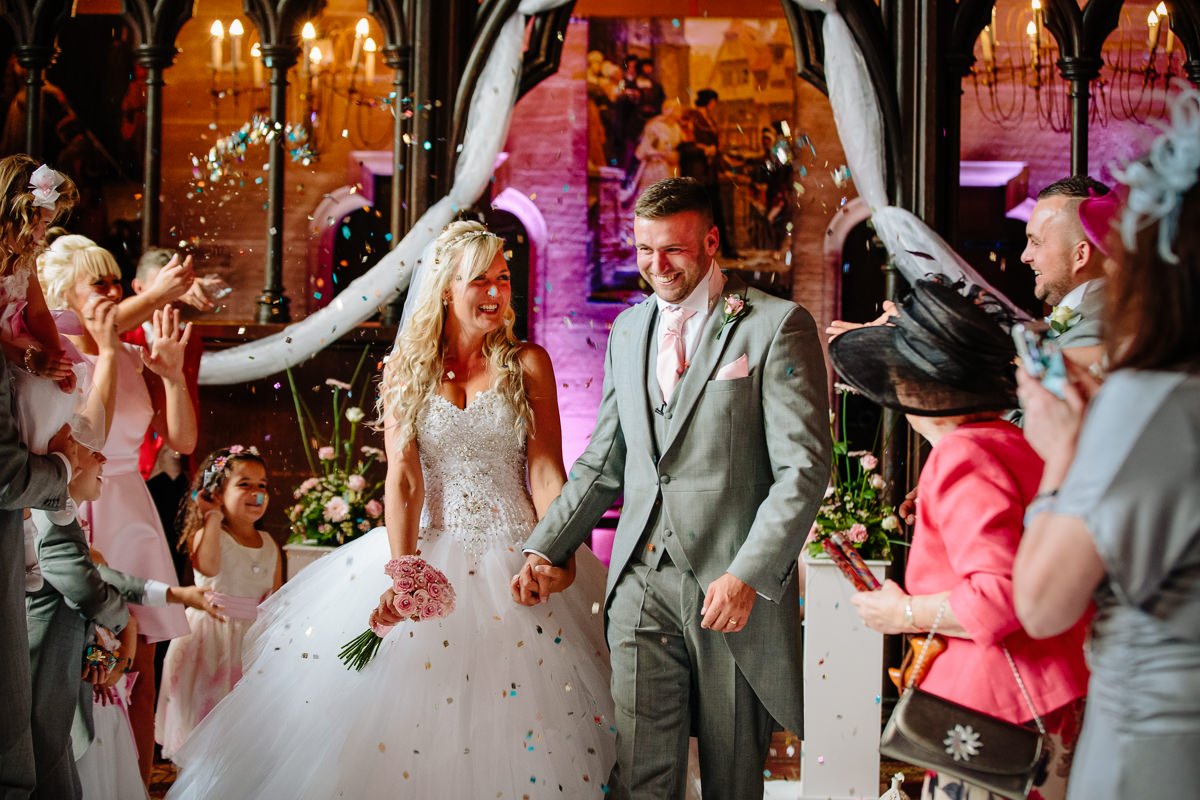 Bride and groom showered with confetti by their wedding guests as they walk down the aisle