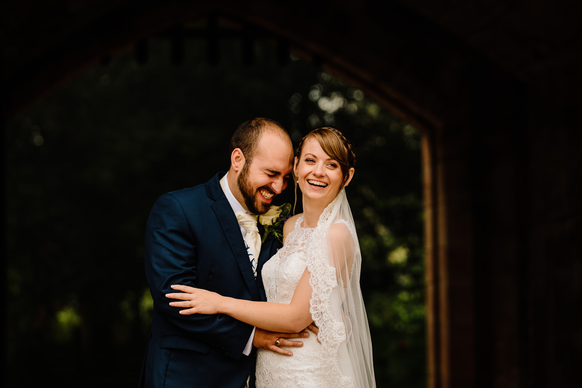 Happy newlyweds laughing together - natural wedding photography