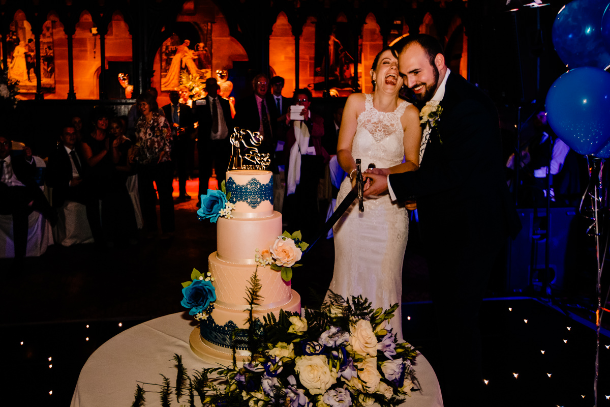 Bride and groom cutting the cake with a sword at Peckforton Castle