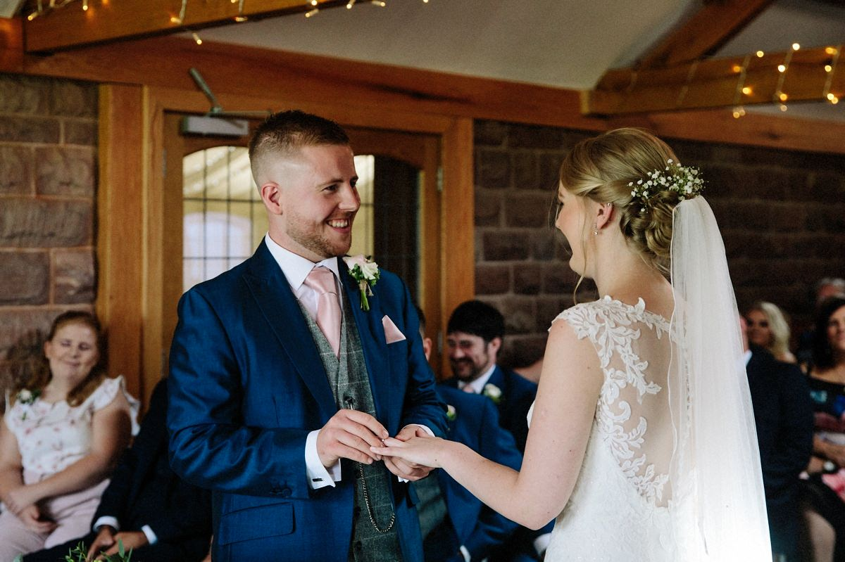 Bride and Groom exchanging wedding rings at Heaton House Farm