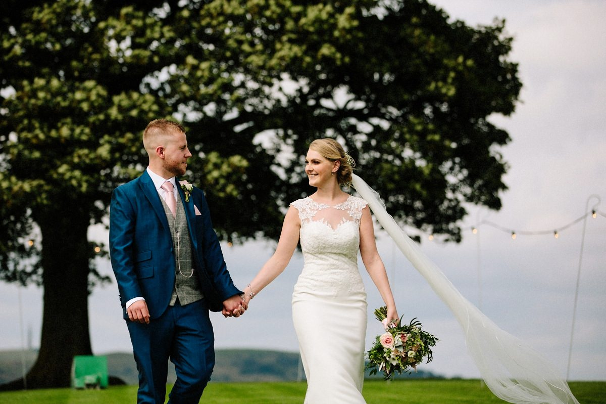 Bride and Groom walking hand in hand at Heaton House Farm