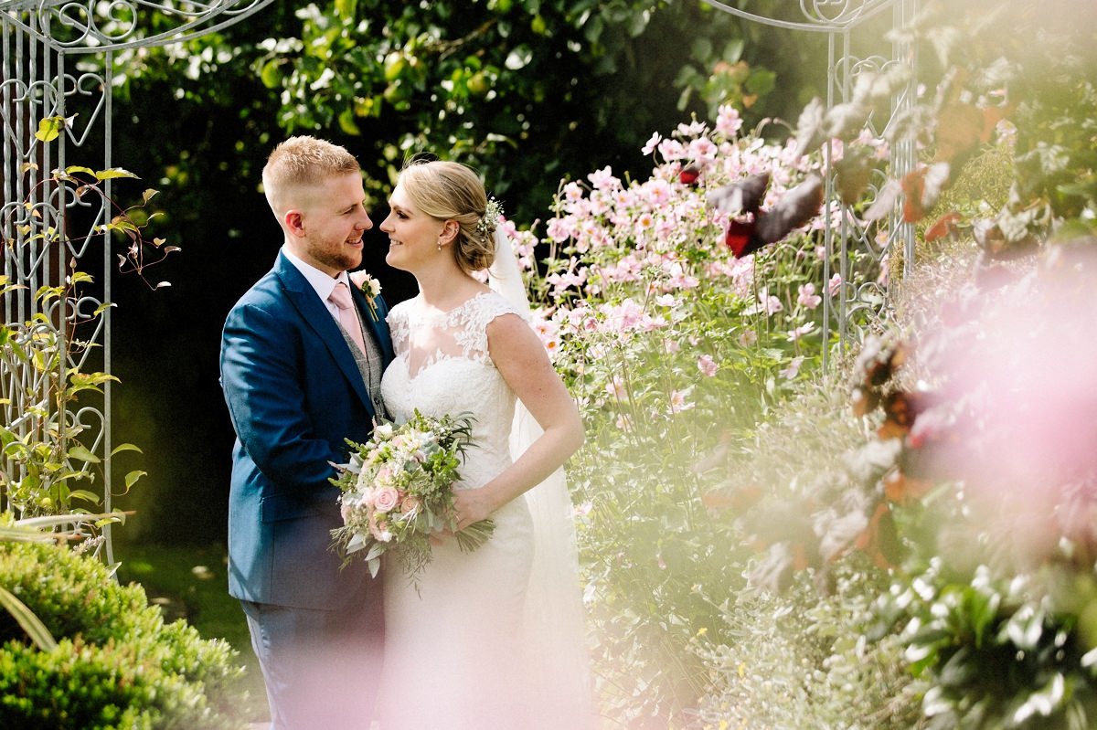 Bride and Groom with pink flowers in the foreground