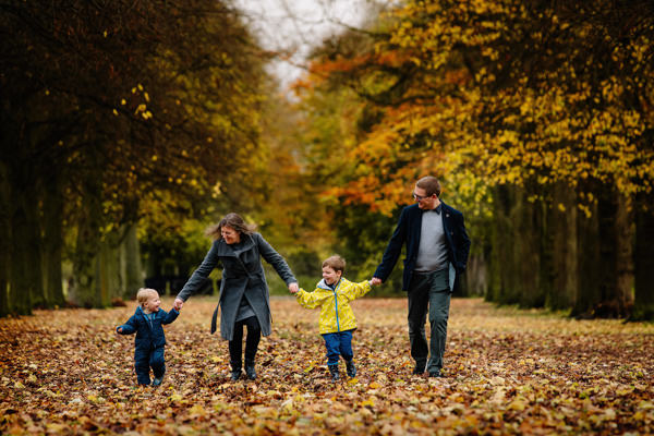 Family walking hand in hand through Marbury Park in Cheshire