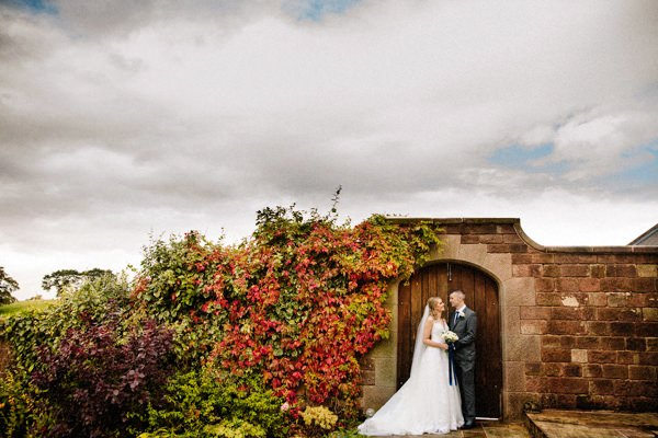 Autumnal Heaton House Farm wedding with the bride and groom holding each other