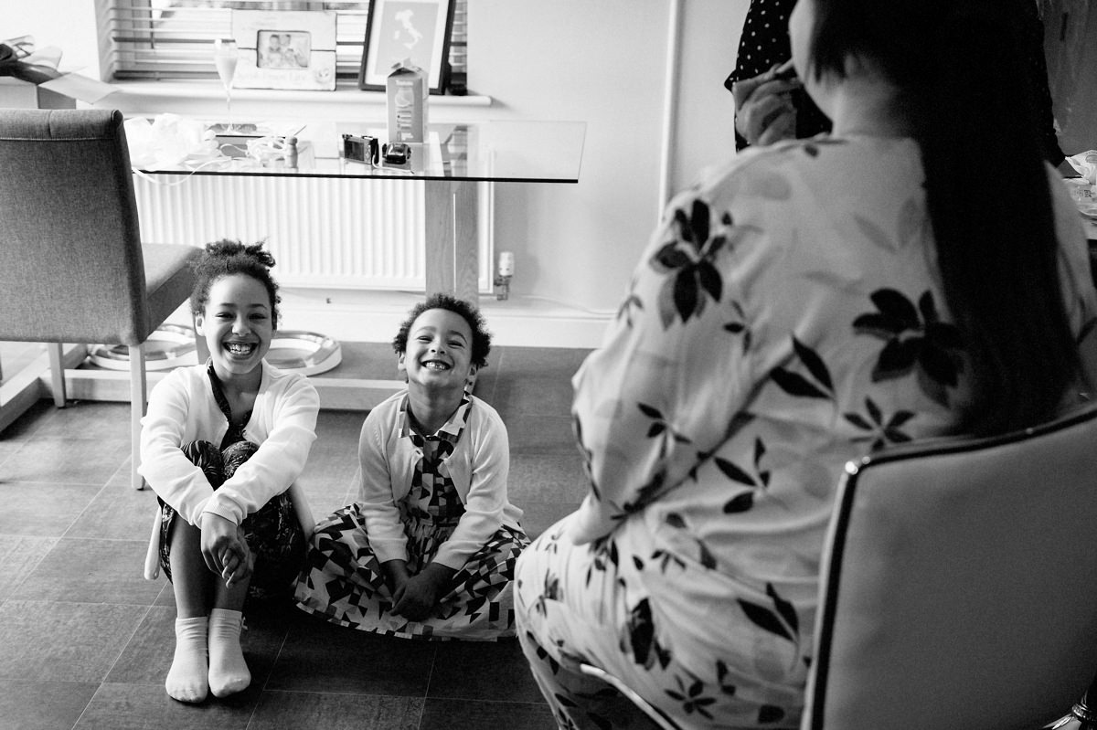 Cute smiling Flower girls watching the bride have her make up applied