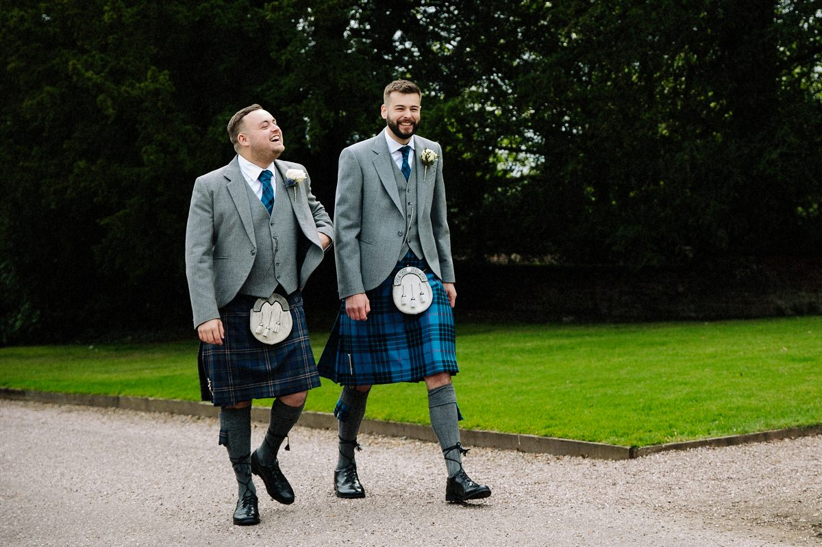 Groom and his best man in kilts laughing together