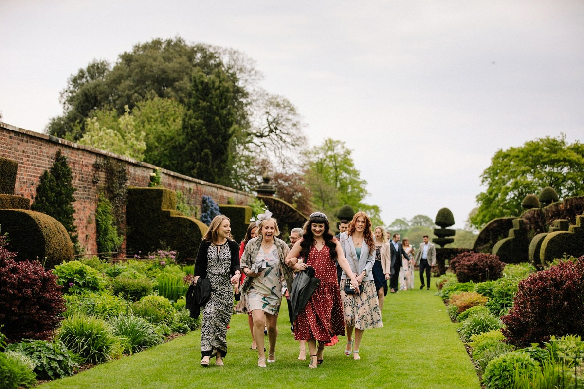 Wedding guests making their way to the alcove for the outdoor wedding ceremony at Arley Hall