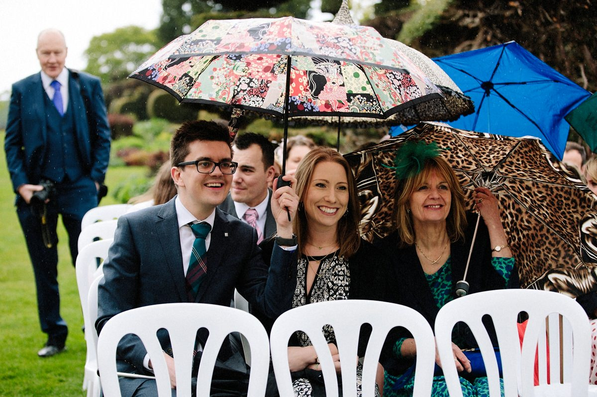 Wedding guests sheltering from the rain under umbrellas