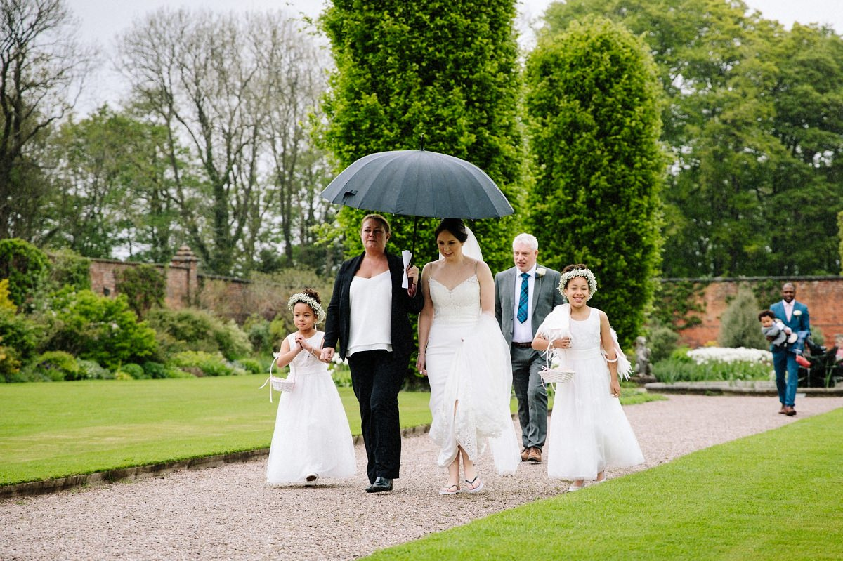 Wedding coordinator sheltering the bride as she makes her way to the alcove for the outdoor wedding ceremony at Arley Hall
