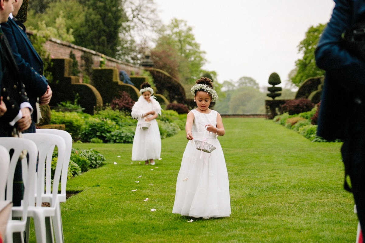 Flower girls showering confetti as they walk down the aisle