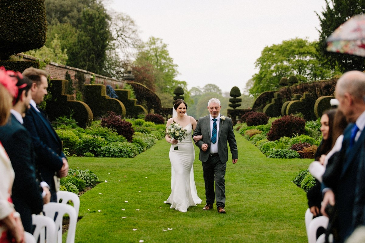 Bride walking down the aisle with her father for the outdoor wedding ceremony at Arley Hall