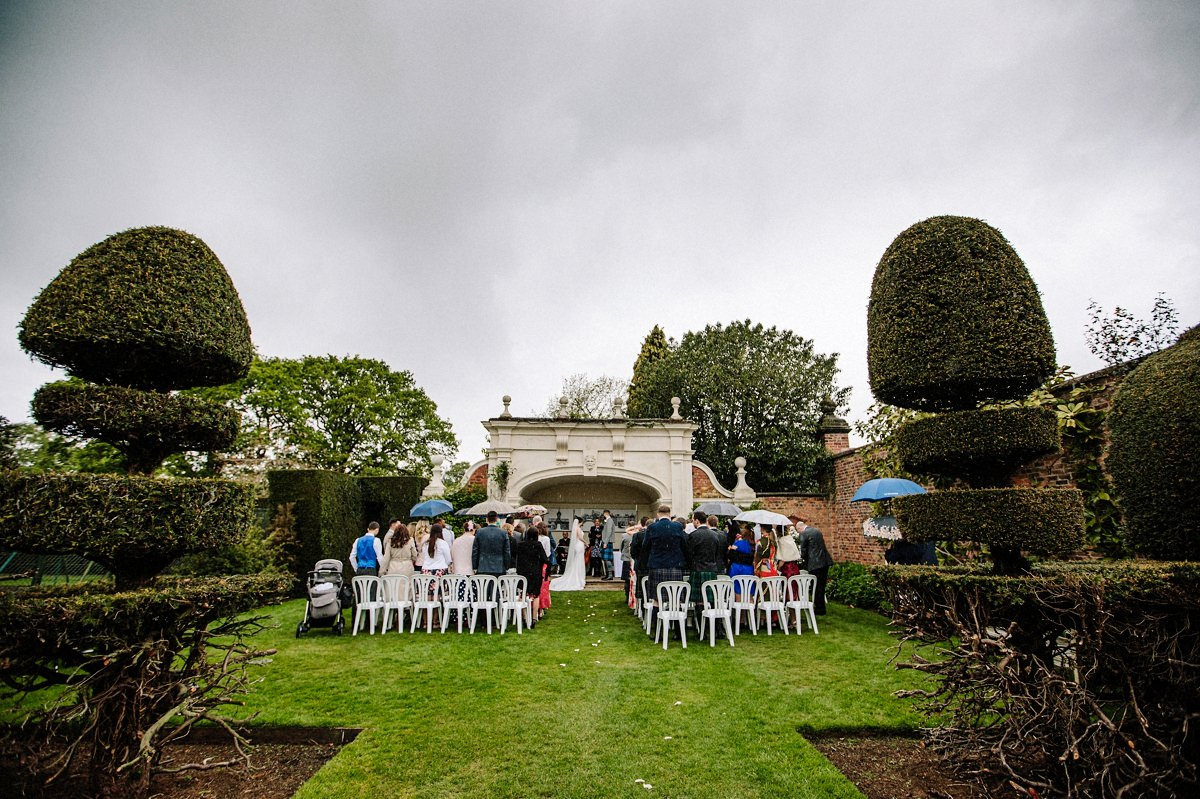 Overview of the alcove and wedding guests for the outdoor wedding ceremony at Arley Hall