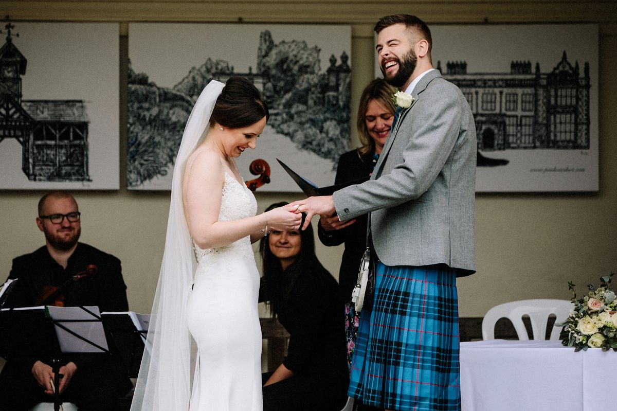 Bride laughing trying to put the wedding ring on the grooms finger
