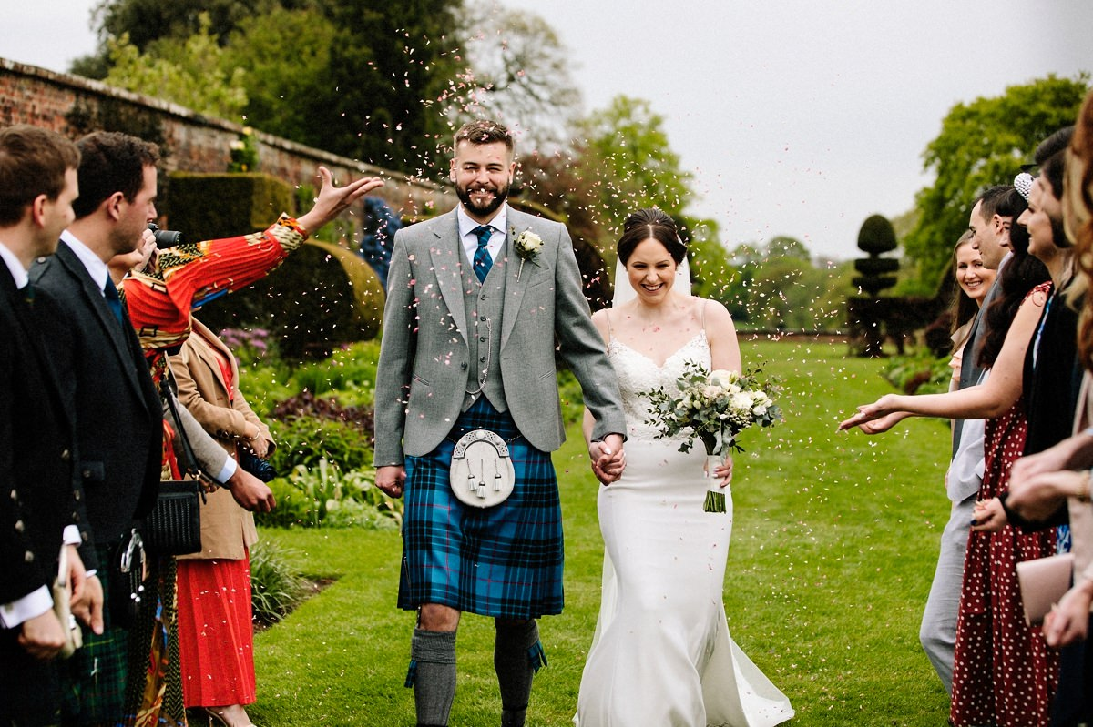 Bride and groom walking down the aisle getting showered with confetti at Arley Hall Gardens