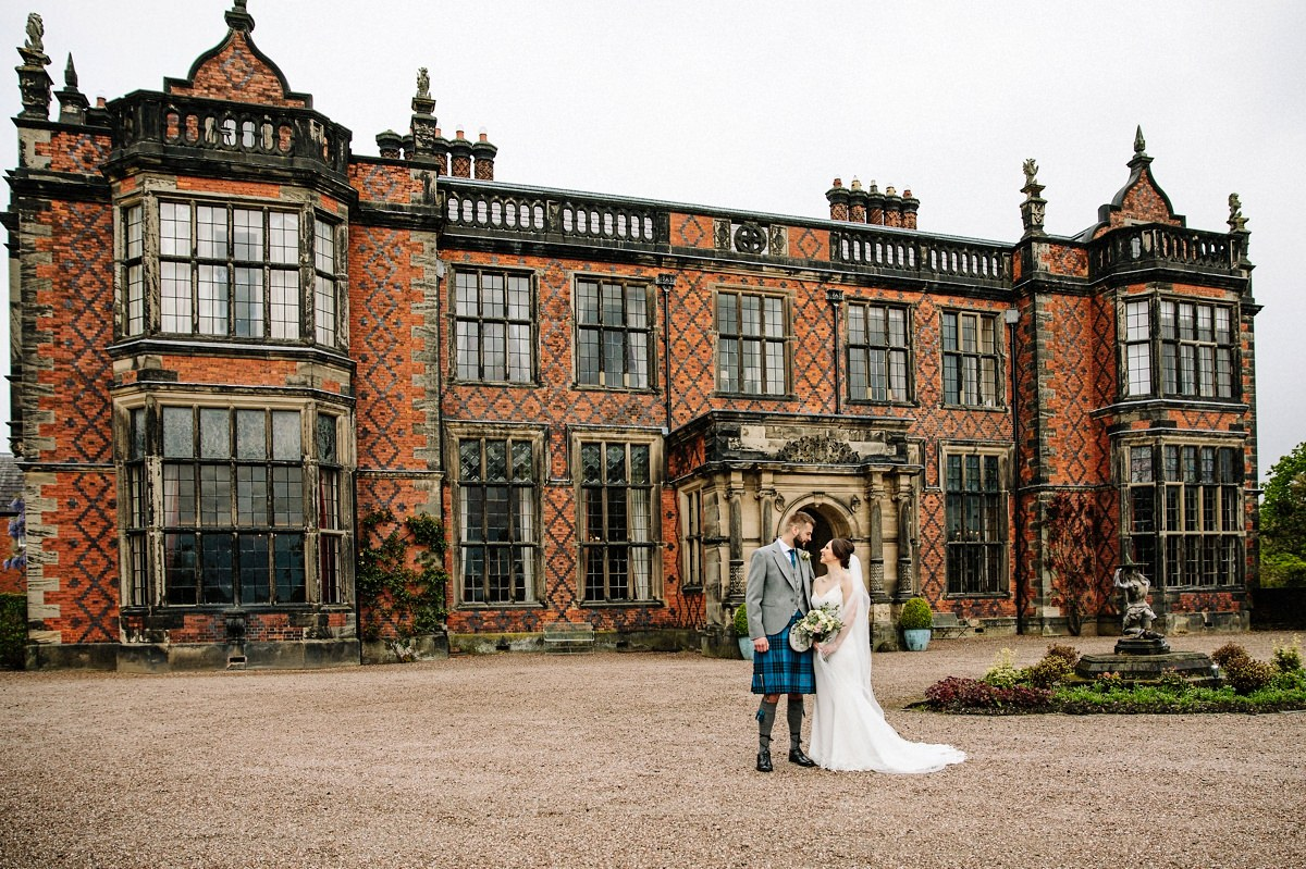 Bride and groom in front of the grand elegant Arley Hall