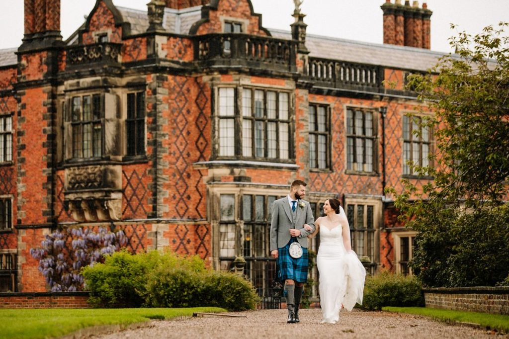 Bride and groom walking linking arms with the stunning Arley Hall in the background
