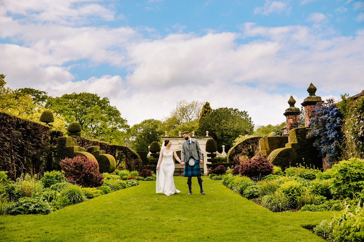 Bride and Groom walking hand in hand in the gorgeous gardens at Arley Hall