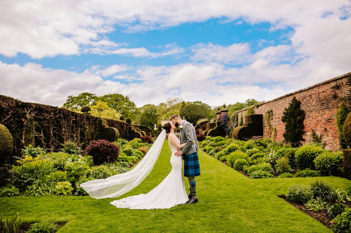 Bride with her wedding veil blowing in the wind with Arley Hall gardens